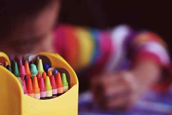 Kind malt mit bunten Stiften