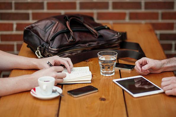Zwei Menschen sitzen am Tisch mit Mobildevices