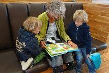Frau liest zwei Kindern vor