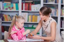 Frau betreut Kind in Bücherei