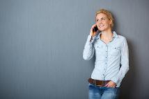 Junge Frau, die mit Mobiltelefon an Tafel lehnt